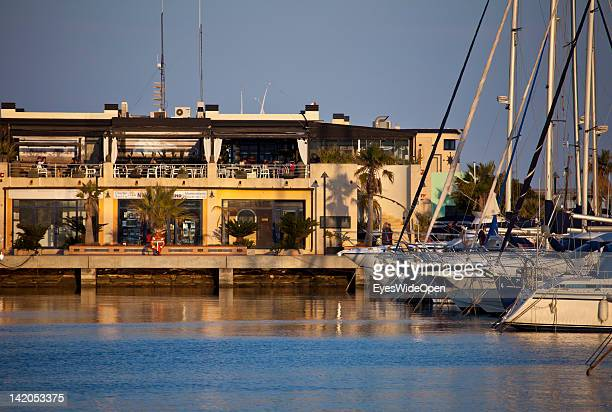Denia Harbour with luxury yachts, fishing boats, tourist sightseeing boats, bars and restaurants on February 21, 2012 in Denia, Spain.