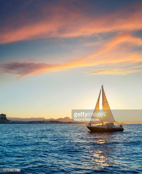denia sunset sailboat from the mediterranean sea alicante spain - sailboat stock pictures, royalty-free photos & images