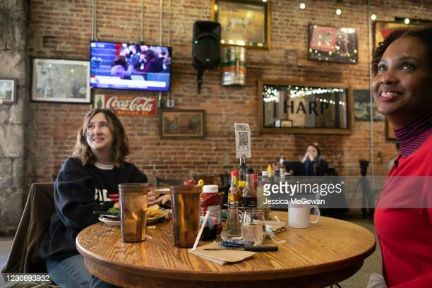 Denice McMillian and Coretta Alexander watch the televised Presidential Inauguration ceremony at Manuel's Tavern on January 20, 2021 in Atlanta,...
