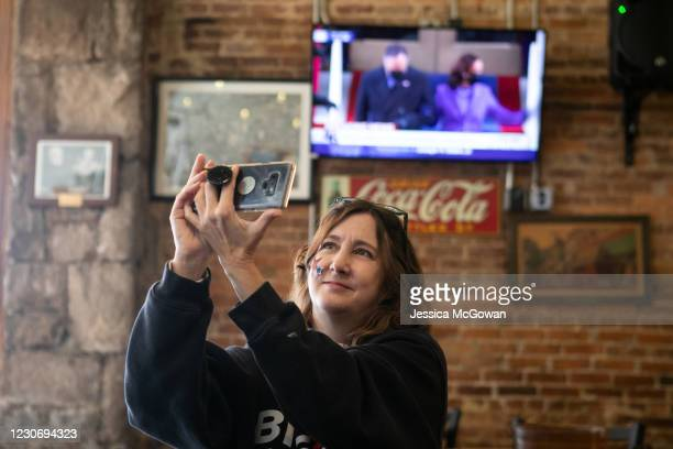 Denice McMillian takes a photo of the television during a watch party at Manuel's Tavern for the televised Presidential Inauguration ceremony on...