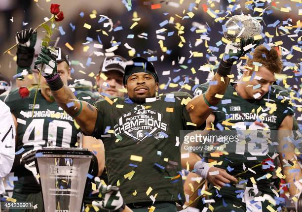 Denicos Allen of the Michigan State Spartans holds up the Big Ten championship trophy after defeating the Ohio State Buckeyes 3424 at the Big 10...