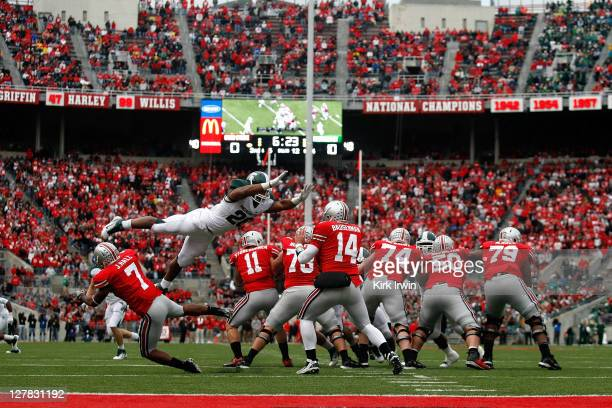Denicos Allen of the Michigan State Spartans leaps over Jordan Hall of the Ohio State Buckeyes on his way to sacking Joe Bauserman of the Ohio State...