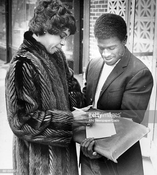 Deniece Williams, an American Grammy Award-winning singer, songwriter and recording producer signing an autograph or papers, 1921.