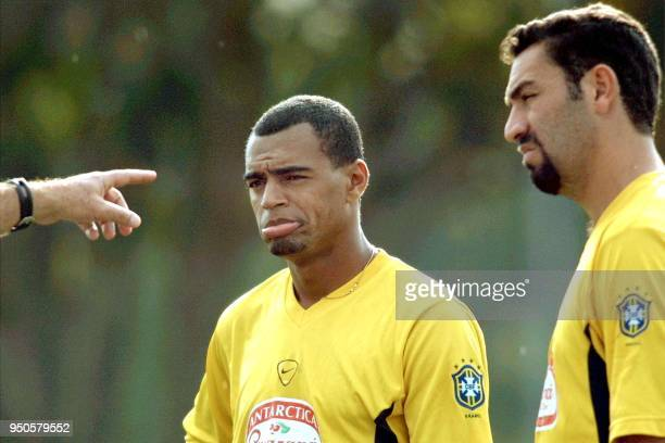 Denilson and Guilherme forward of the Brazilian soccer team listen to instructions 21 July 2001 during a practice in Cali Colombia Brazil will play...