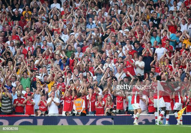 Denilson of Arsenal celebrates his goal with teammates in front of the Arsenal fans during the Barclays Premier League match between Arsenal and...