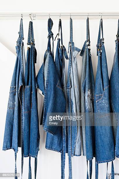 Denim aprons hanging in a row