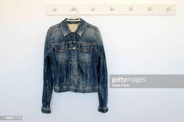 denim jacket hanging on rack - chaqueta fotografías e imágenes de stock