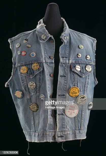 Denim vest with twenty-three pinback buttons pinned across the front. The vest is made of light blue denim. It has two front breast pockets with...