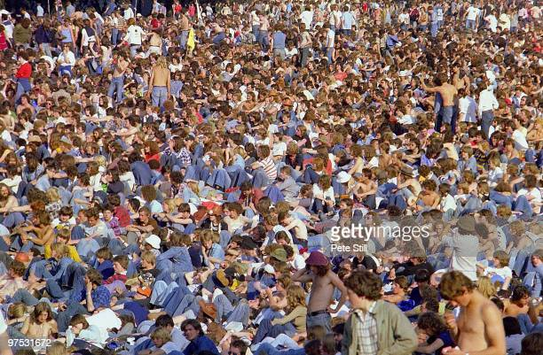 A denim wearing audience of 1970s rock festival goers sit in the sunshine at Knebworth during the support for Led Zeppelin on August 4th 1979 in...