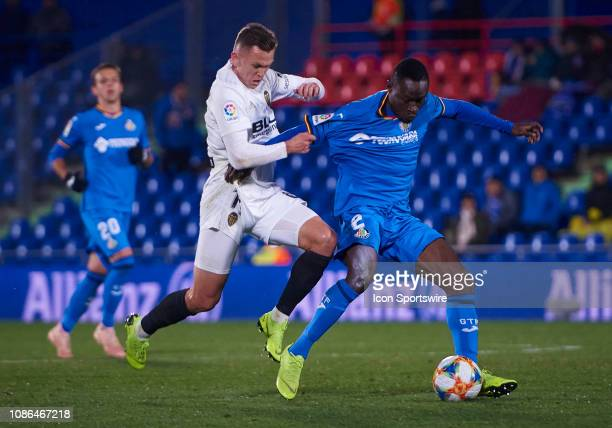 Denis Cheryshev forward Valencia CF competes for the ball with Djene Dakoman Ortega defender of Getafe CF during the Copa del Rey match between...