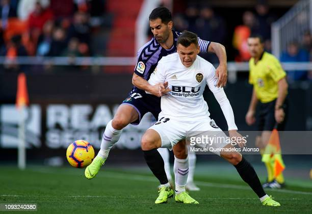 Denis Cheryshev of Valencia CF competes for the ball with Javier Moyano of Real Valladolid during the La Liga match between Valencia CF and Real...