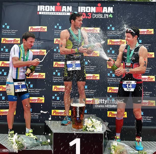 Denis Chevrot of France celebrates winning the Ironman triathlon event alongside Markus Thomschke of Germany and Kevin Thornton of Ireland on August...