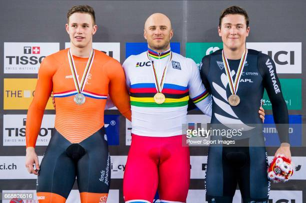 Denis Dmitriev of Russia celebrates winning the Men's Sprint Final's prize ceremony with Harrie Lavreysen of the Netherlands and Ethan Mitchell of...