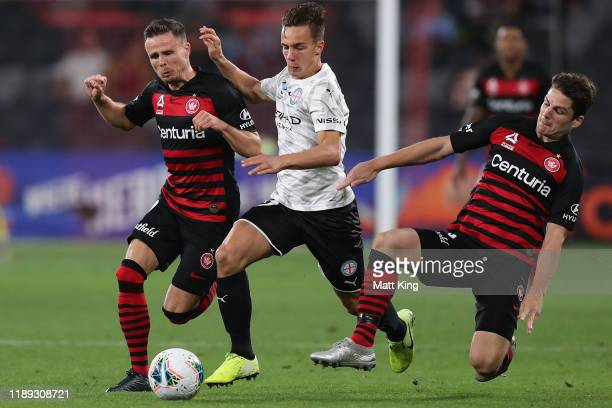 Denis Genreau of Melbourne City FC is tackled by Nicolai Muller and Pirmin Schwegler of the Wanderers during the round 7 A-League match between the...