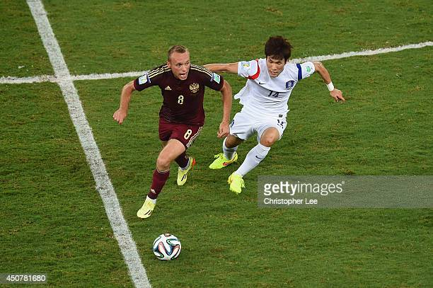 Denis Glushakov of Russia controls the ball against Han KookYoung of South Korea during the 2014 FIFA World Cup Brazil Group H match between Russia...