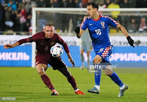 Denis Glushakov of Russia is challenged by Nikola Kalinic of Croatia during the international friendly football match between Russia and Croatia at...
