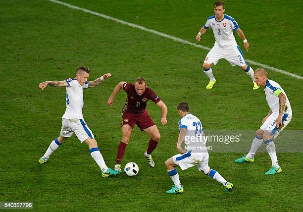 Denis Glushakov of Russia is surrounded by Slovakian players during the UEFA EURO 2016 Group B match between Russia and Slovakia at Stade...