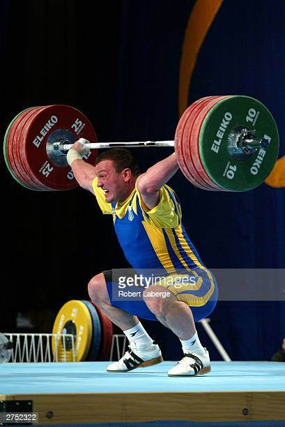Denis Gotfrid of Ukraine twists his left elbow as he attempts to lift 195 Kilograms at the Snatch during the Men's 105 KG Group A competition at the...