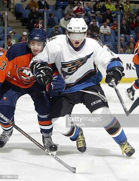 Denis Grebeshkov of the New York Islanders and Alex Ovechkin of the Washington Capitals fight for position during their game at the Nassau Coliseum...