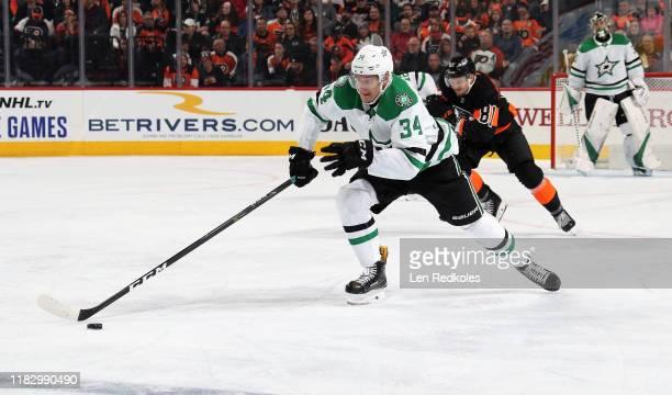 Denis Gurianov of the Dallas Stars skates the puck against Carsen Twarynski of the Philadelphia Flyers on October 19, 2019 at the Wells Fargo Center...