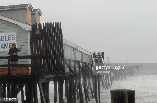 Denis Hromin stands on a pier to get a picture of the beach during Hurricane Irene August 27, 2011 in Kill Devil Hills, North Carolina. Hurricane...