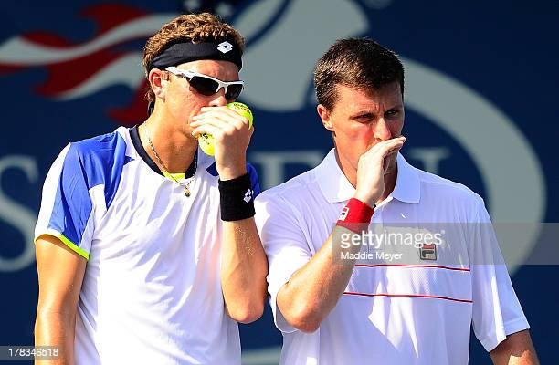 Denis Istomin of Uzbekistan and Ken Skupski of Great Britain talk tactics during their men's doubles first round match against Jaroslav Levinsky and...