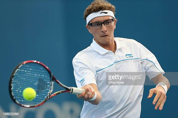 Denis IstomIn of Uzbekistan plays a backhand during his match against Andy Murray of Great Britain on day six of the Brisbane International at Pat...