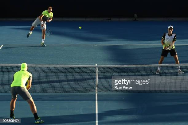 Denis Istomin of Uzbekistan serves in his first round men's doubles match with Mikhail Kukushkin of Kazakhstan against Sam Groth of Australia and...