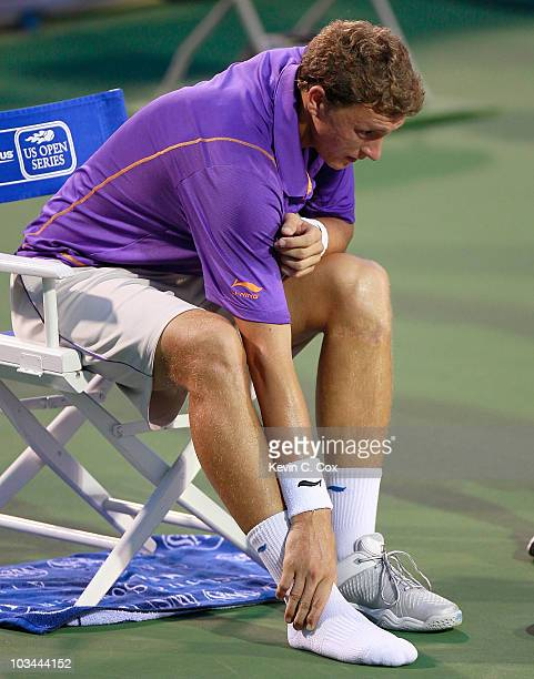 Denis Istomin of Uzebekistan sits down after rolling his right ankle in his match against Roger Federer of Switzerland during Day 3 of the Western...