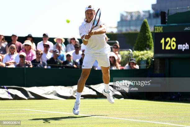 Denis Kudla of The United States returns to Lucas Pouille of France during their Men's Singles first round match on day one of the Wimbledon Lawn...