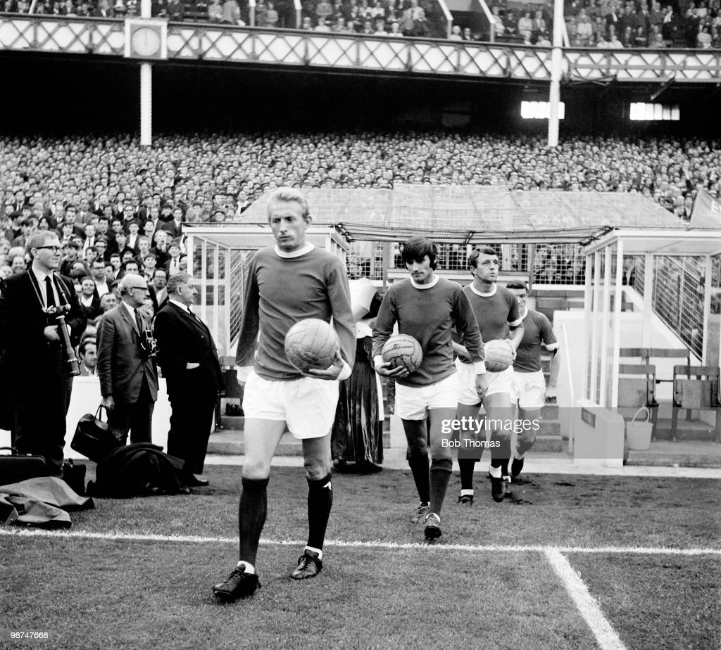 Denis Law is followed by George Best and David Herd as Manchester United enter the field at Goodison Park prior to their match against Everton, in Liverpool, circa 1968.