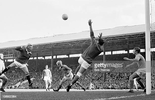 Denis Law of Manchester United heads the ball past Ipswich Town goalkeeper David Best during their Division One match played at Old Trafford...