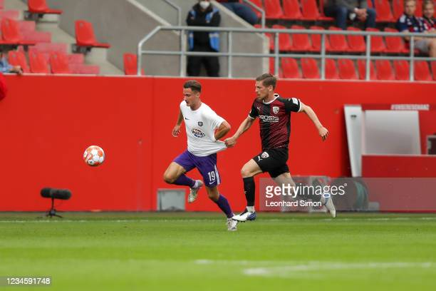 Denis Linsmayer of FC Ingolstadt 04 and Omar Sijari of Erzgebirge Aue in action during the DFB Cup first round match between FC Ingolstadt 04 and...