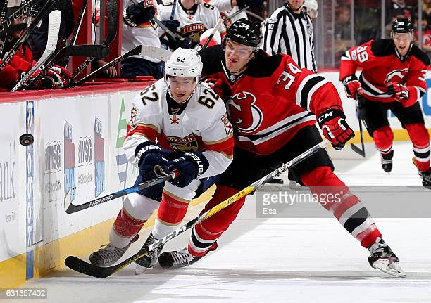 Denis Malgin of the Florida Panthers is hit by Steven Santini of the New Jersey Devils in the first period on January 9 2017 at Prudential Center in...