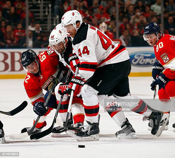 Denis Malgin of the Florida Panthers tangles with Mark Fraser of the New Jersey Devils and teammate Miles Wood at the BBT Center on October 13 2016...