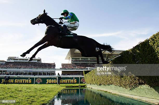 Denis O'Regan rides BLACK APALACHI over the water jump during The John Smith's Maghull Novices' Steeple Chase on the third day of the Grand National...