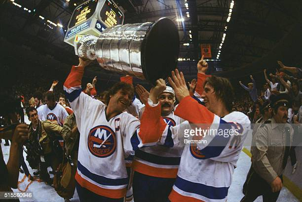 Denis Potvin, Bryan Trottier, and Mike Bossy, members of the New York Islanders hockey team, carry the Stanley Cup trophy in 1981.