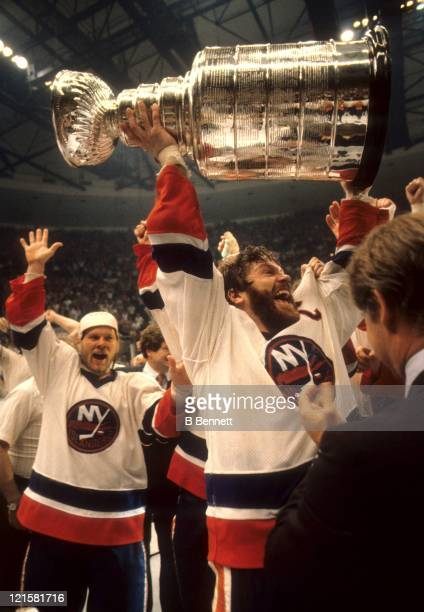 Denis Potvin of the New York Islanders celebrates with the Stanley Cup Trophy as teammate Butch Goring waits his turn to hold the cup after the...