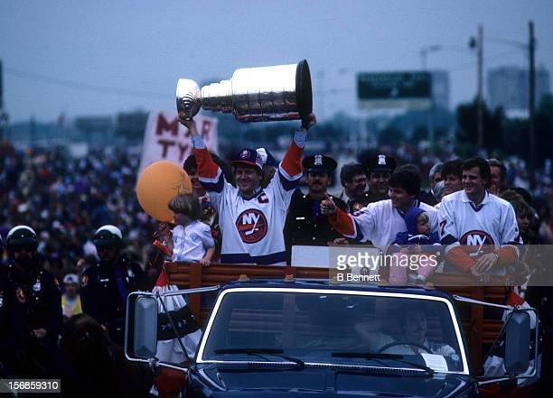 Denis Potvin of the New York Islanders shows the Stanley Cup Trophy to the crowd during the 1983 Stanley Cup Parade after they defeated the Edmonton...