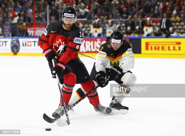 Denis Reul of Germany challenges Sean Couturier of Canada during the 2017 IIHF Ice Hockey World Championship Quarter Final game between Canada and...