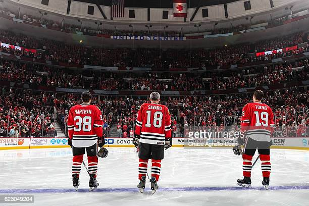 Denis Savard hockey Hall of Famer stands in between Ryan Hartman and Jonathan Toews of the Chicago Blackhawks while being honored during the Chicago...