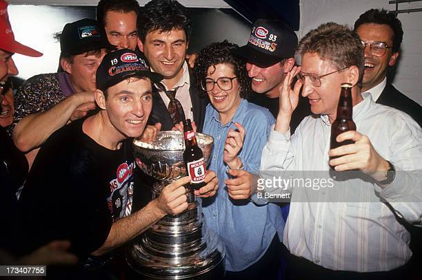 Denis Savard of the Montreal Canadiens celebrates with the Stanley Cup Trophy in the locker room after defeating the Los Angeles Kings in Game 5 of...