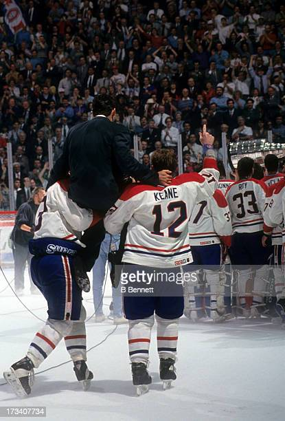 Denis Savard of the Montreal Canadiens is lifted onto the shoulders of Brian Bellows and Mike Keane as their teammates celebrate with the Stanley Cup...