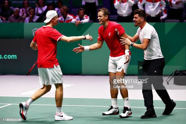 Denis Shapovalov and Vasek Pospisil of Canada celebrate victory with Canada team captain Frank Dancevic in the semi final doubles match between...