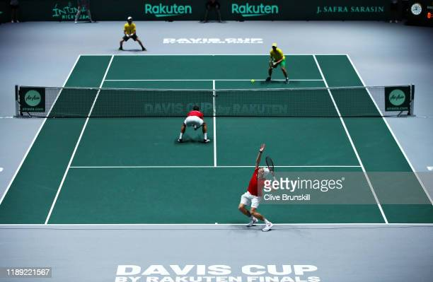 Denis Shapovalov of Canada serves alongside doubles partner Vasek Pospisil in the quarter final doubles match between Australia and Canada during Day...