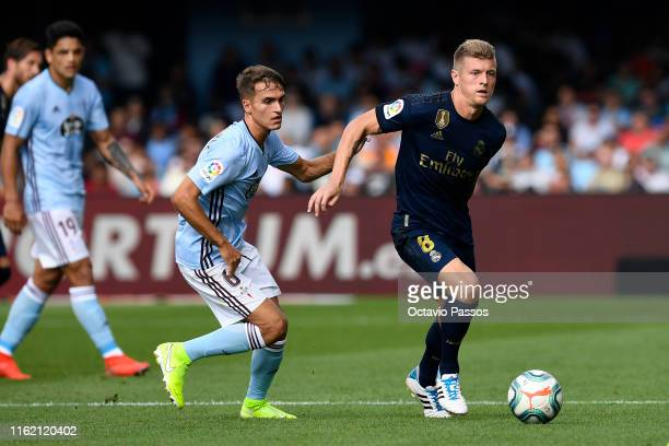 Denis Suarez of RC Celta competes for the ball with Toni Kroos of Real Madrid during the Liga match between RC Celta de Vigo and Real Madrid CF at...
