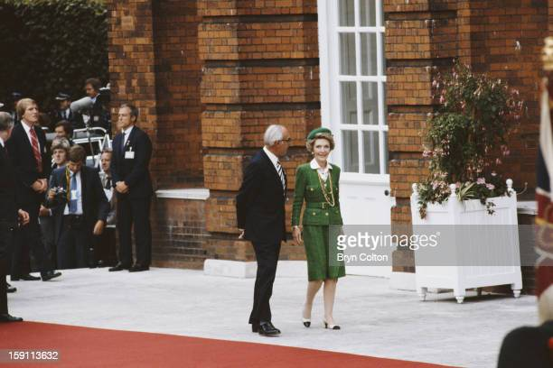 Denis Thatcher husband of British Prime Minister Margaret Thatcher with US First Lady Nancy Reagan as they arrive for the opening ceremony at...
