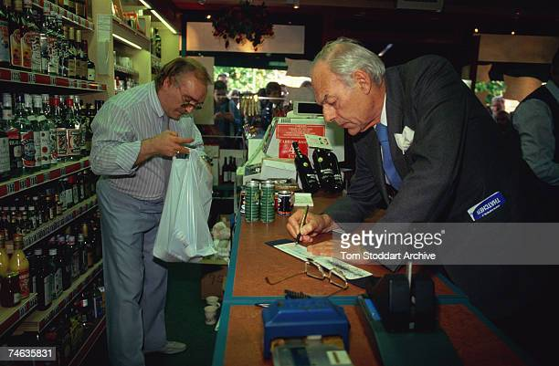 Denis Thatcher husband of Prime Minister Margaret Thatcher writing a cheque in an off license circa 1985