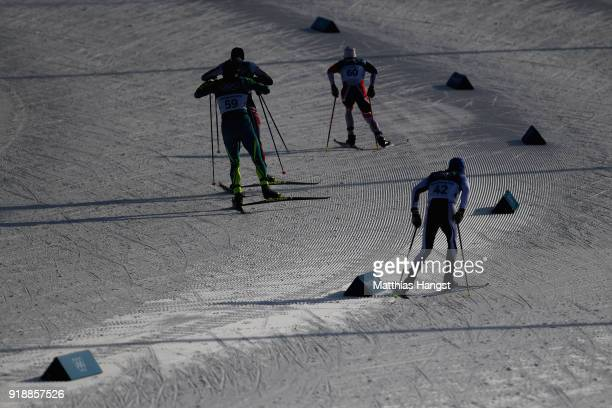 Denis Volotka of Kazakhstan Simen Hegstad Krueger of Norway and Matti Heikkinen of Finland compete during the CrossCountry Skiing Men's 15km Free at...
