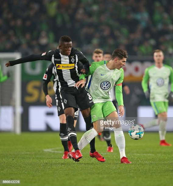 Denis Zakaria Lako Lado of Borussia Moenchengladbach and Mario Gomez of Wolfsburg battle for the ball during the Bundesliga match between VfL...